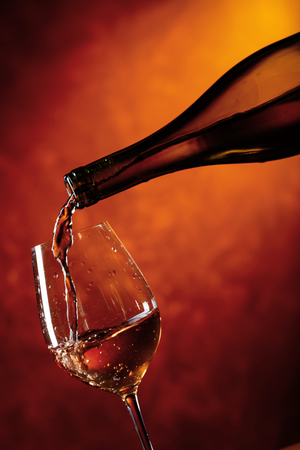 Glass of wine being poured from a bottle . Copy space  . Stock Photo