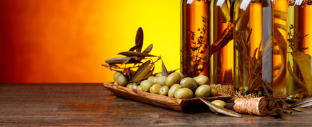 Green olives and bottles of olive oil with spices and herbs. Copy space. Foto de archivo