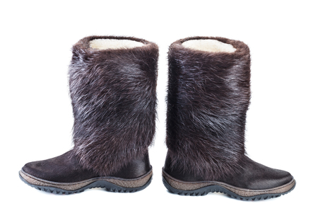 Warm boots from natural fur of nutria isolated over white background .