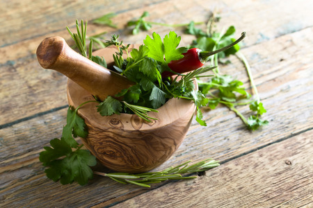 Wooden mortar with rosemary, coriander, thyme and parsley.