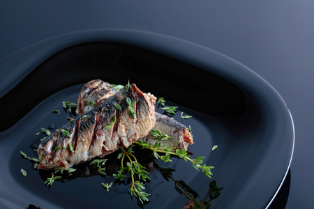 Grilled sardines with olive oil and thyme on a black plate. Foto de archivo