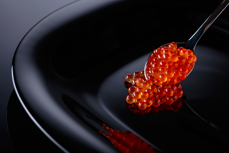 Red caviar in spoon on a black background.