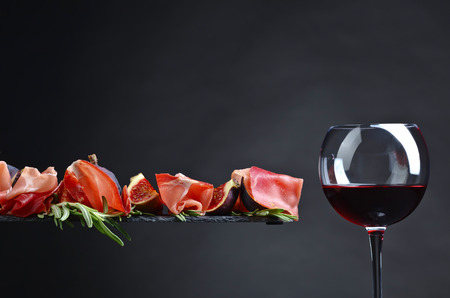 Prosciutto with figs, red wine and rosemary on a dark background.
