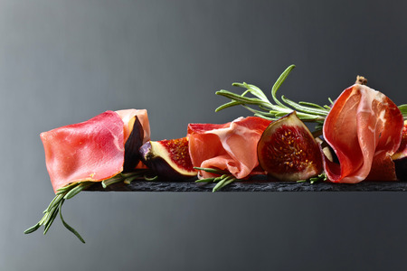 Prosciutto with figs and rosemary on a dark background. Copy space .