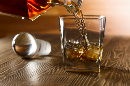 Whiskey with ice on old wooden table.