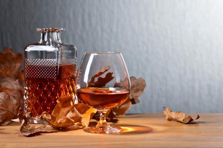 ブランデーと古い木製のテーブルの上にオークの葉を乾燥。コピースペース :