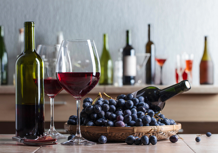 Red wine and grapes on a kitchen table.
