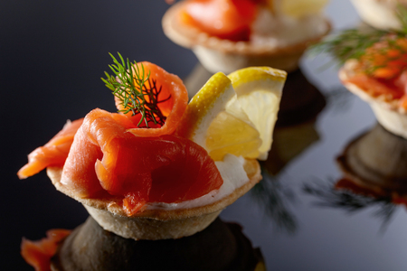 Tartlets with salmon , cream and a slice of lemon on a black background.