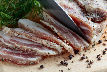 Slices of salty bacon with spices on a wooden table. Stock Photo
