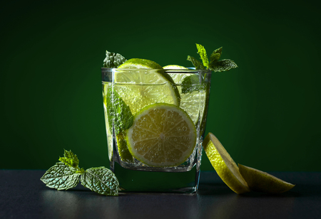 Cocktail with lime , ice  and mint on black table in bar.