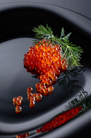 Red caviar with dill on a black plate.