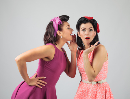 Two young women whispering gossip . Expressive emotion , Studio shot.