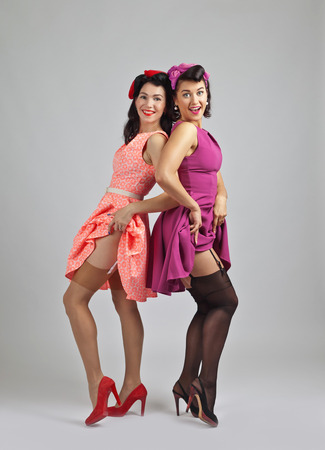 Beautiful women in pin up style with perfect hair and make up .Expressive facial expressions. Фото со стока
