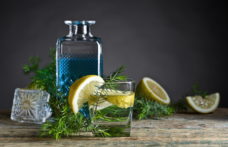 Cocktail with blue gin , tonic and lemon on a old wooden table .  Stock Photo