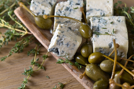 Blue cheese , capers and thyme on a wooden table .