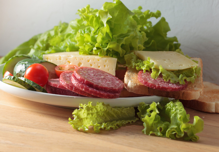 Healthy eating sandwich for breakfast with salami , cheese, tomatoes , cucumbers and lettuce .