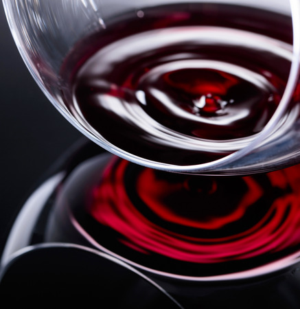 Glass of red wine, macro shot , black reflective background. Фото со стока