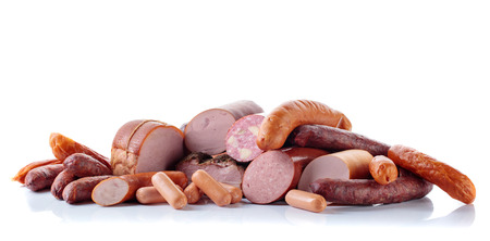 Different sausages and smoked meats isolated on white background .
