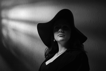 Dramatic portrait of a beautiful woman in hat with perfect hair and makeup . Studio shot .