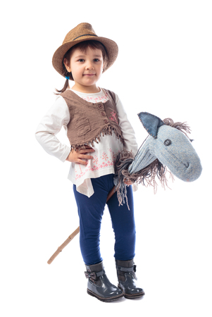Cute little girl dressed like a cowboy playing with a homemade horse. Isolated on a white background. Expressive facial expressions.