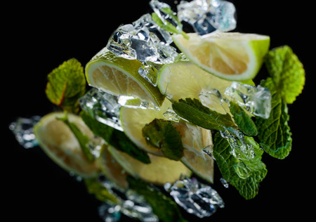 Lime pieces with leaves of mint on a black background. Selective focus. Stock Photo