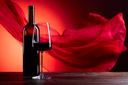 Glasses and bottle of rede wine on a red background. Red sheer fabric flutters in the wind. Copy space.