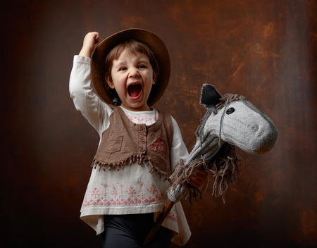 Cute little girl dressed like a cowboy playing with a homemade horse. Expressive facial expressions.