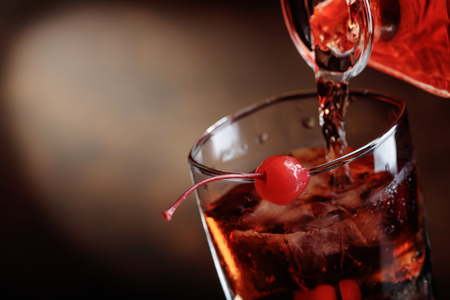 Whiskey is poured from a carafe into a glass with ice.Cocktail Manhattan with cherry.Copy space. Foto de archivo