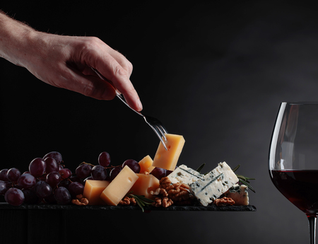 Glass of red wine with various cheeses , grapes and walnuts on a black background. Foto de archivo