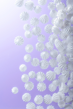 French vanilla meringue cookies on purple background with copy space. Top view.