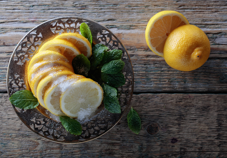 Lemon slices with sugar and mint leaves on a wooden table. Top view , copy space.