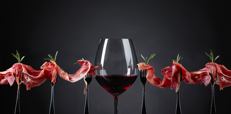 Prosciutto with rosemary and glass of red wine on a dark background. Copy space for your text. Фото со стока