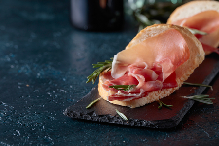Sandwich with prosciutto and rosemary on a dark background.