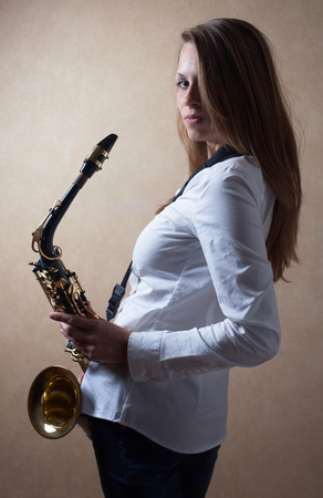 Young beautiful long haired blonde in white shirt with saxophone.