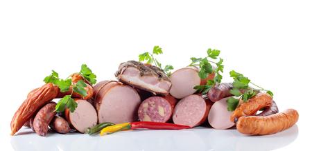 Diferentes embutidos y carnes ahumadas aisladas sobre fondo blanco.