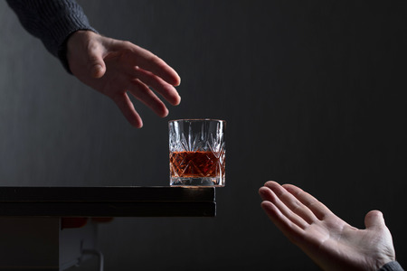 Man's hand reaches for a glass of alcohol. Conceptual image on the subject of alcoholism. Copy space for your text.