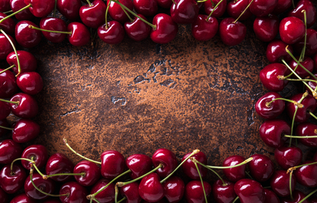 Cherry Background.  Sweet organic cherries on old copper table. Copy space, top view.