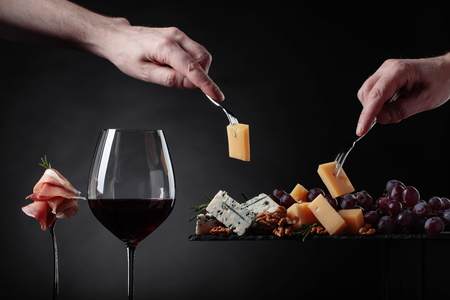 Glass of red wine with various cheeses , fruits and prosciutto on a black background. Foto de archivo