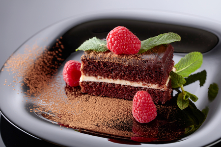 Chocolate cake with raspberry and mint on a black plate.