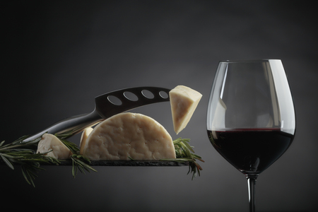 Sheep cheese with rosemary and glass of red wine on a black background.