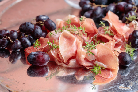 Italian prosciutto crudo or jamon with thyme and grapes on a metal platter .
