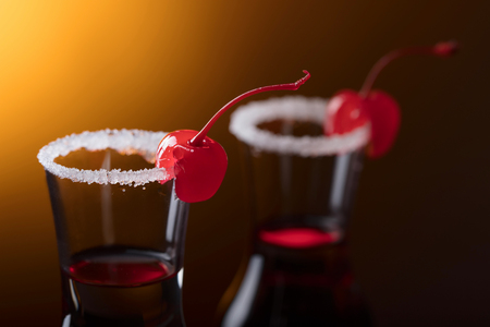 Sweet cherries on glasses of liquor garnished with sugar . Copy space for your text. Archivio Fotografico