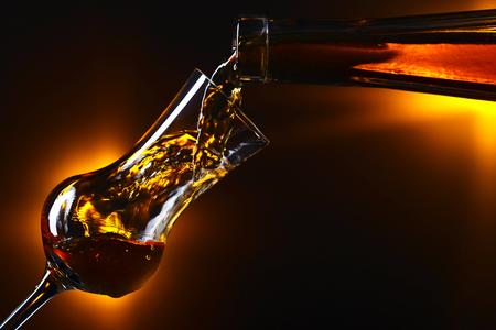 Gießen von Alkohol in ein Weinglas auf dunklem Hintergrund