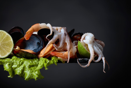 Glass of white wine, mixed delicious seafood, salad and lime slices on a black background. Copy space for your text.