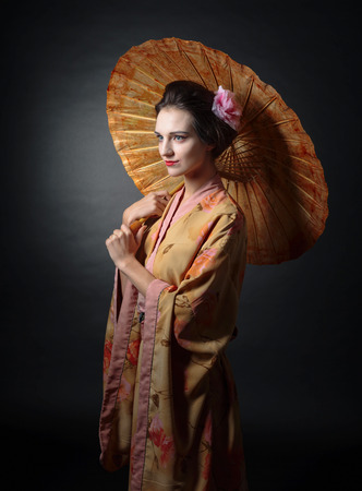Young beautiful woman in traditional japanese kimono with umbrella on a black background.