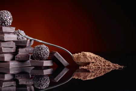 Pralinen, gebrochene Schokoladenstücke und Löffel mit Kakaopulver auf schwarzem, reflektierenden Hintergrund. Standard-Bild