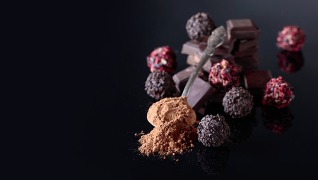 Chocolate candies, broken chocolate pieces and spoon with cocoa powder on a black reflective background. Archivio Fotografico