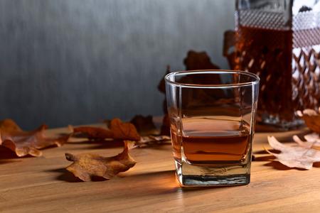 Whisky y hojas secas de roble sobre una vieja mesa de madera. Copia espacio