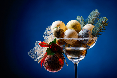 Christmas balls in wineglass on a dark blue background. Copy space .