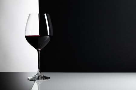 Glass of red wine on a reflexive background, copy space for your text.
